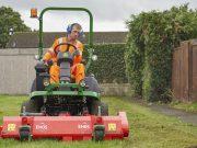 Grounds maintenance, grounds person cutting grass