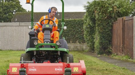 Grounds maintenance, grounds person cutting grass
