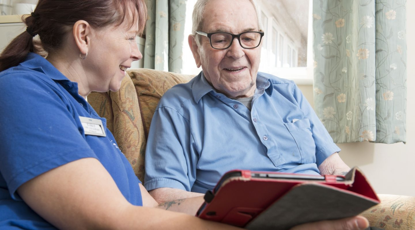 NorseCare employee using an iPad with a resident