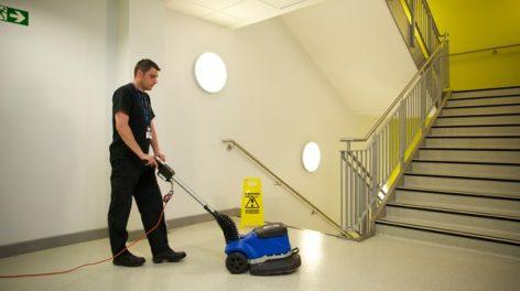 Cleaner using floor buffer in school hallway